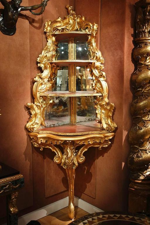 Substantial gilded wood corner console embellished with intertwining curls and leaves. The upper portion is composed of four receding triangular shelves whose exterior edge is in the same shape as the base of the console. The edge of each shelf is