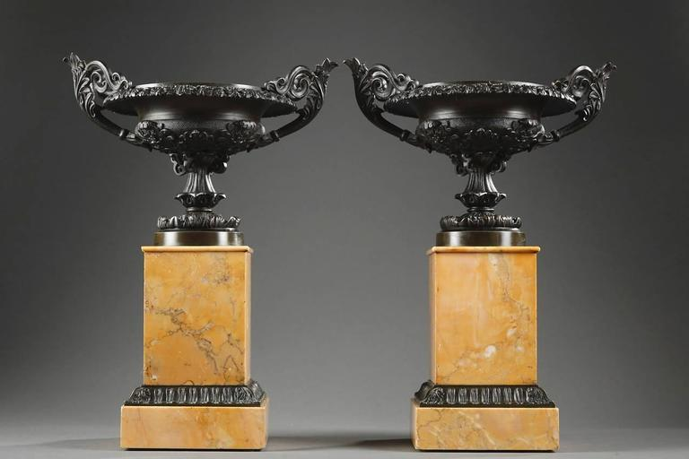 Pair of patinated bronze Louis-Philippe cassolettes. Each cassolette has two scrolling handles and rests on a quadrangular Sienna marble base. The basin, à l'antique, is decorated with acanthus leaves, palmettes and foliage,   circa