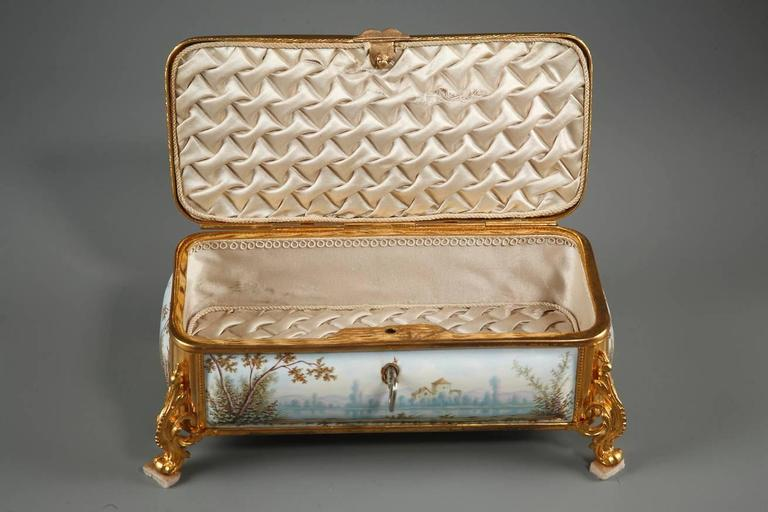 Rectangular Limoges enamel box with its key and gilt bronze mounts. The box rests on four curved, sweeping feet that are richly decorated with volutes and foliage. The entire surface of the lid is decorated with a scene depicting two characters on a