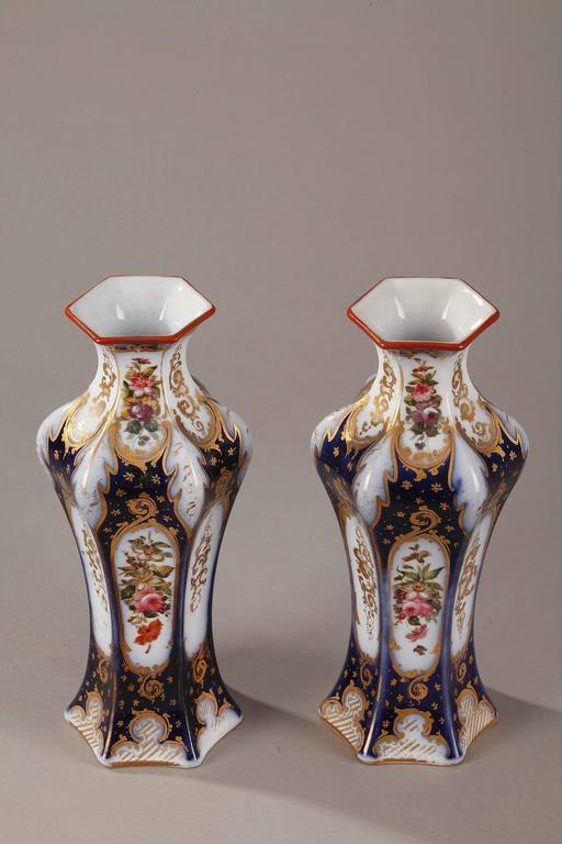 Pair of hexagonal porcelain vases decorated with multicolored flowers. The midnight blue background is highlighted with gilded floral motifs and foliage. Napoleon III period. Light wear to the gilding,  circa 1860. Dimensions: L: 10 cm, P: 10 cm,