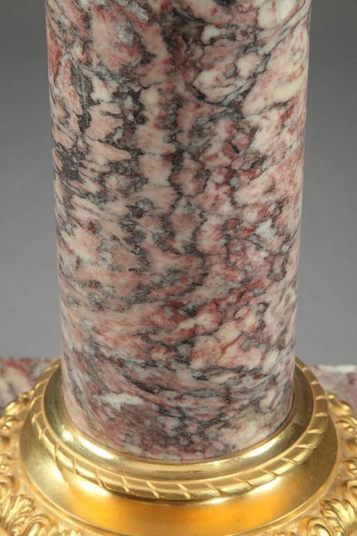 Brocatelle marble display column with sculpted and gilt bronze cap and base. The capital is embellished with ovals and fluting, and the base is decorated with alternating ovals and palmettes. The ensemble is set on a square, terraced base. Napoleon