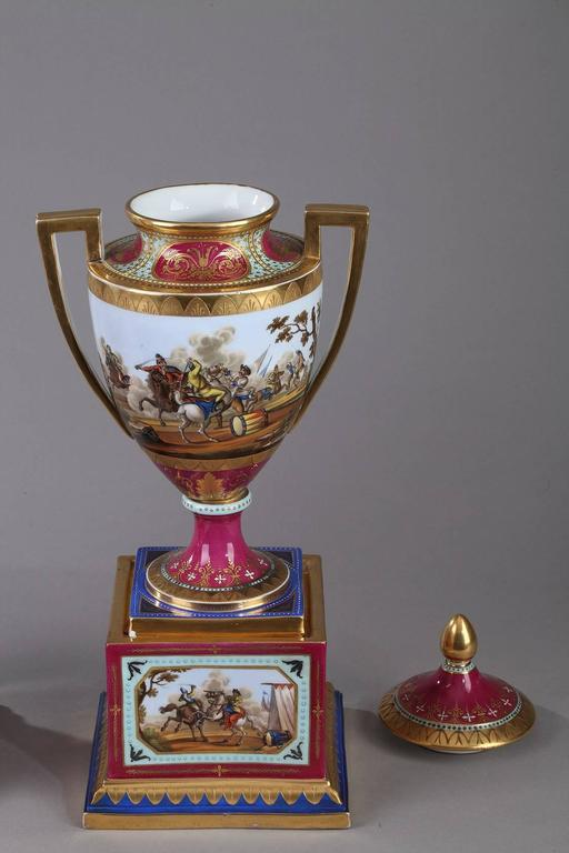Pair of porcelain vases with removable lid. They are embellished with multicolored friezes depicting scenes of battle probably drawn from the history of Austria and its conflicts with the Ottoman Empire. The collar and base are decorated with gilded