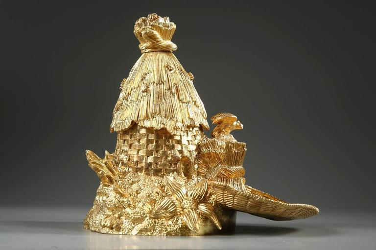 Small, gilt bronze inkwell in the shape of a hive. The inkwell cover is decorated with sheaves of wheat with bees resting on top. The base is adorned with flowers and vegetation. The inkwell has two small receptacles with their lids, one of which