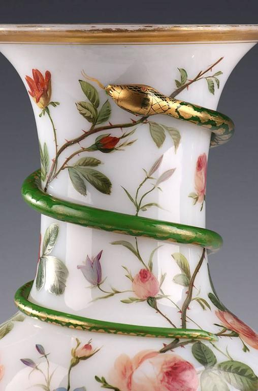 Impressive pair of baluster-shaped vases in white enamel opaline, decorated with red and blue flowers and snakes that wind up around the high collar. The collar and the base are encircled with gold bands. Light wear to the gilding,     circa