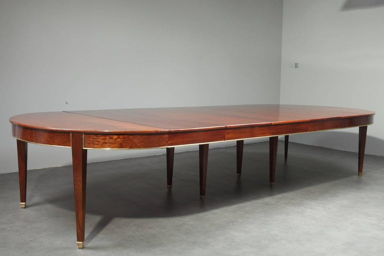 Large mahogany and mahogany veneer dining room table for 8 to 18 seats settings from the Directory period. It is decorated with brass stripes. The table is provided with five leads in mahogany veneer that are each almost 20 inches wide (50 cm), and