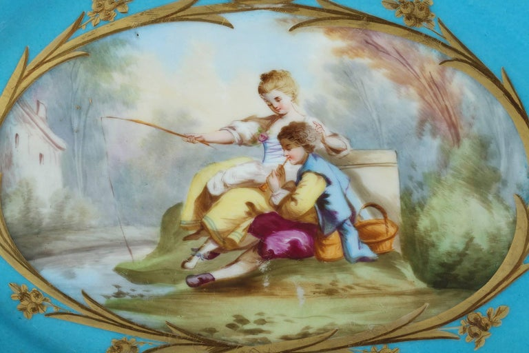 Oval blue? porcelain ?cup with polychromatic decoration composed of a large cartouche with gilt-decorated borders depicting a man and a young woman in a landscape, sitting on the grass near a lake. The woman is fishing while her lover is playing the