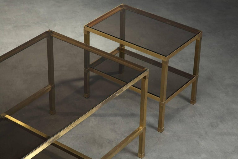 Gilt bronze coffee table composed of three nesting tables. Each table is provided with two smoked glass trays. Attributed to Maison Jansen (Paris, 1880-1989). Good vintage condition, with some oxidation on the metal, circa 1970. Measures: Big table