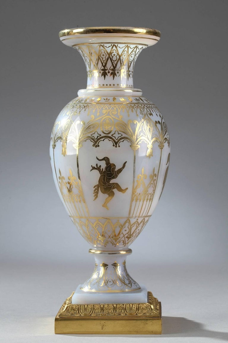 Pair of white Opaline vases decorated with gilded Gothic arcades and medieval figures playing music or dancing. Each vase rests on a square gilt bronze base decorated with foliage. This delicate decoration was produced by the Jean-Baptiste Desvignes