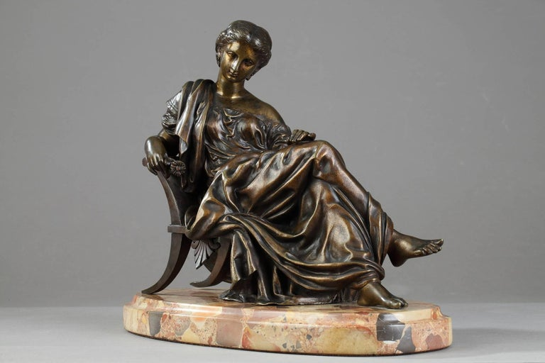 Bronze statue with gold colored patination featuring a seated classical lady after James Pradier (1790-1852). She is set on an oval Breche d'Alep marble base. This bronze is inspired by Sappho, a marble statue realized by Pradier in 1852, which is
