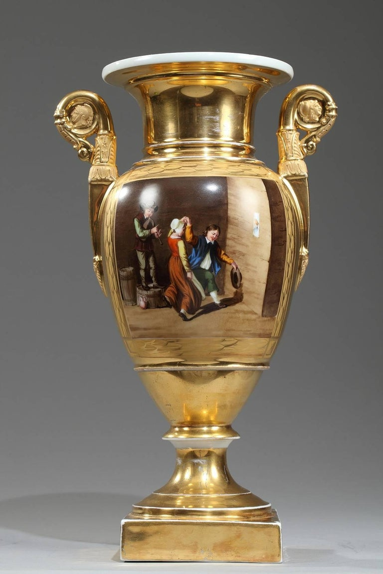 Early 19th century? porcelain? baluster-shaped vases set upon a high foot and a square base. Each vase has two gold tones and polychromatic decoration of interiors scenes with women and men playing, drinking and dancing. Scrolling handles decorated