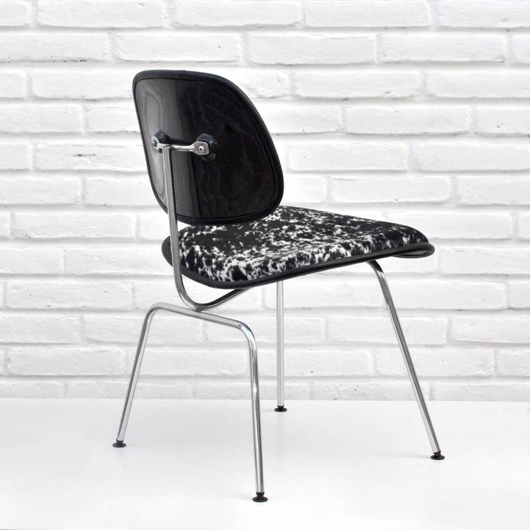 A classic DCM chair designed by Charles and Ray Eames for Herman Miller. The chair is upholstered in black and white cowhide with black leather trim, a steel body and black feet.  Chair is marked underneath.