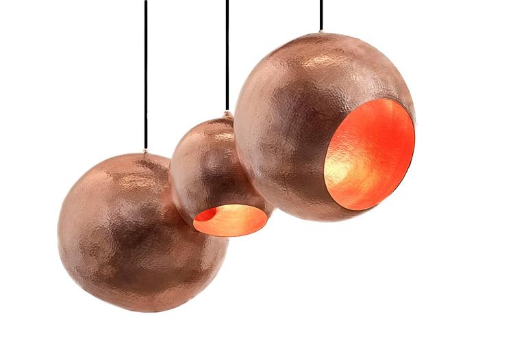 A stunning hand-hammered pendant light with three internal lamps. Its organic shape and warm light contrasts nicely with the polished copper finished. 
