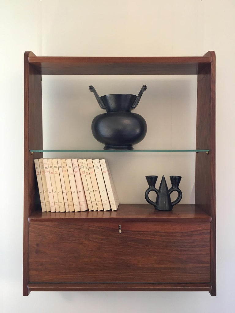 A walnut wall-mounted shelf, with a glass shelf on brass support, above a close cupboard opening with an abattant, with its working original key. Denmark, circa 1955.