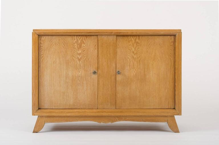 A limed oak buffet, opening with two doors, revealing a central shelf, with its two original keys France, circa 1940.