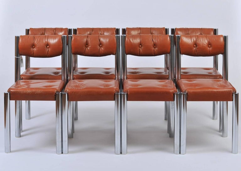 A set of eight chrome and brown leather dining chairs, the polished chrome frames supporting very comfortable padded buttoned seats and backs,