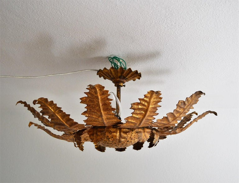 Exceptional beautiful and rare pendant lamp in the form of a thistle made of strong gilt metal leafs. Made in Italy, circa 1960s. Hollywood Regency style.  This big flower lamp is a handmade artist work of cut rough iron leafs, rivet together to