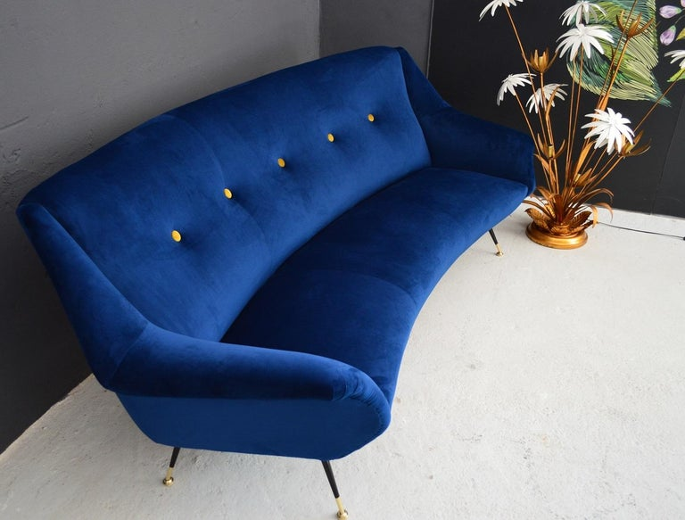 A magnificent round-shaped original sofa from the 1960s with the typical shape of the midcentury Italian years. The sofa was completely gutted and completely restored with the best materials. The outside was redone with soft Italian royal blue