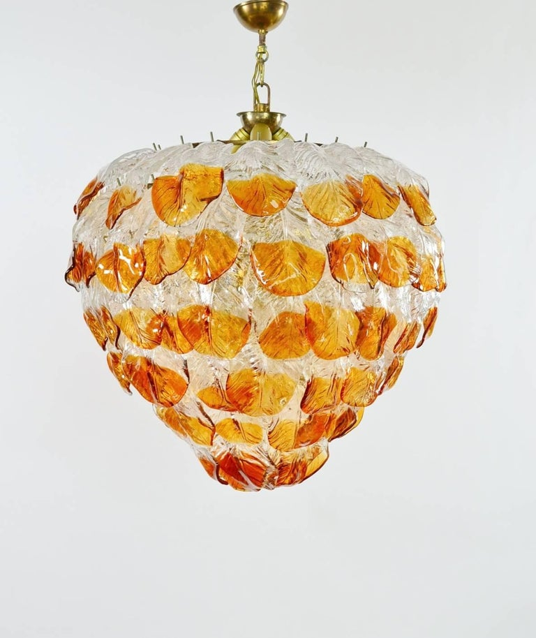 This gigantic Murano glass chandelier was produced in Italy during the 1960s. Due to its quality it has been attributed to Mazzega production. It is made of a solid iron case with brass finish and keeps exactly 99 big handcrafted leafs made of
