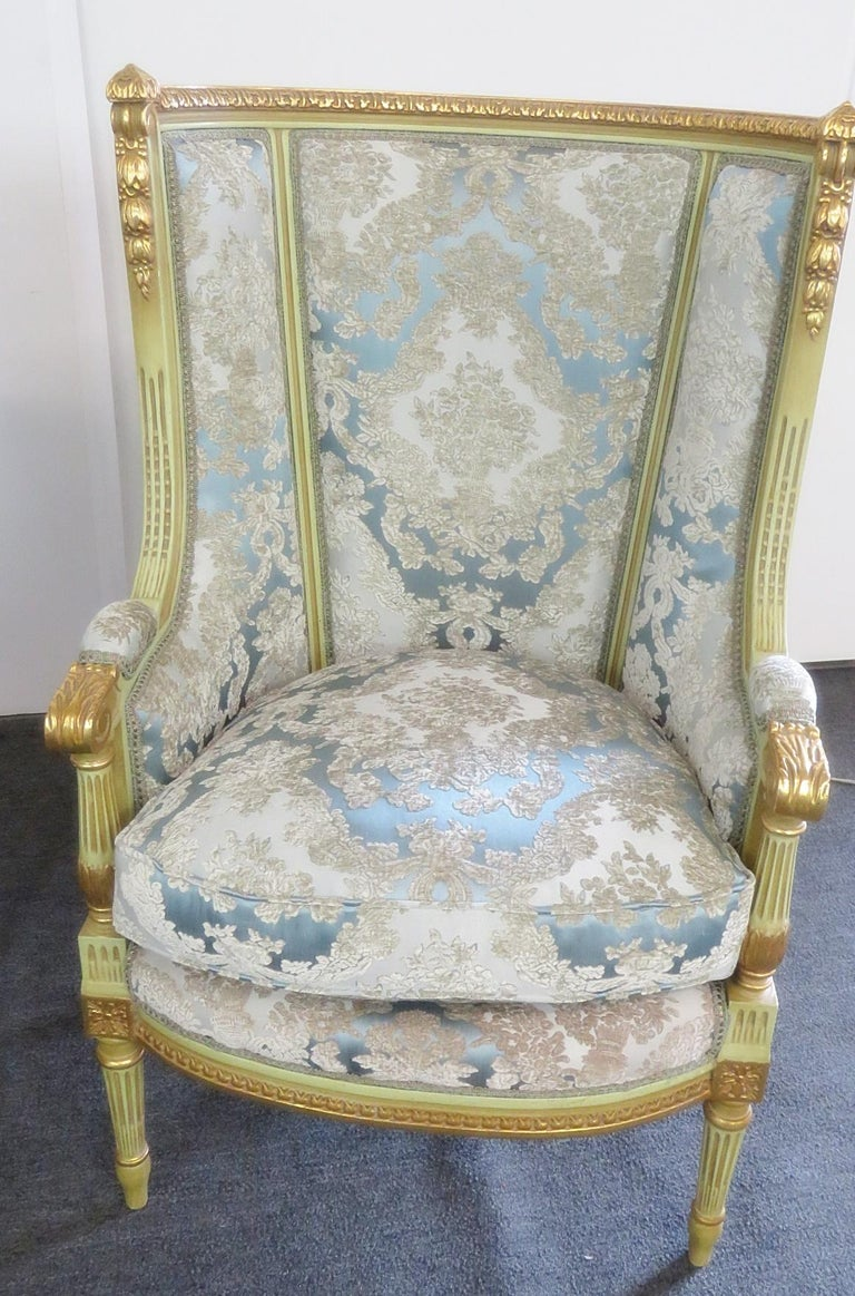 Pair of Louis XVI style paint decorated wing back chairs with gilt accents and textured upholstery.