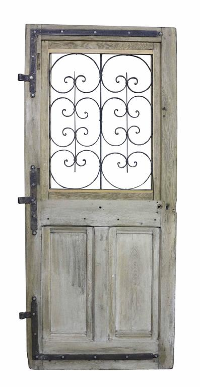 Oak door with wrought iron window grill and hinges. Not currently glazed.(Please note that the glass is not insured in transit outside of the UK).