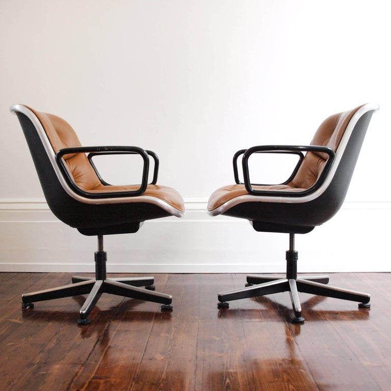 Charles Pollock's Executive chair is a timeless design for both the home and the office. Offering complete comfort- this pair of tan leather upholstered swivel chairs feature a brushed aluminium outer rim, with a matte black plastic back and glossy