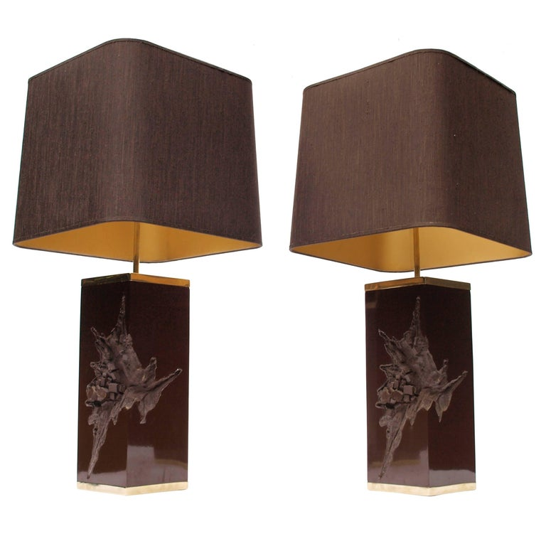A grand pair of chocolate brown Philippe Cheverny lamps from the late 1970s cast in resin and cased on the top and bottom in gold metal edging. Finished with beautiful extending brass finials. With brown silk, gold lined lampshades.