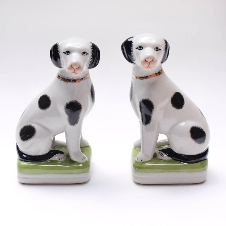 A pair of 1950s painted mantle dog ornaments with hand painted features and a gold gilt collar. These ornaments are a 20th century take on the Victorian Staffordshire pottery hearth spaniels.