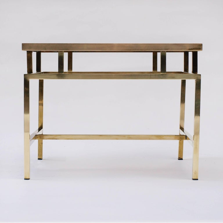 A brass and smoked glass coffee table in the style of Maison Jansen, with a geometric frame and tiered top.