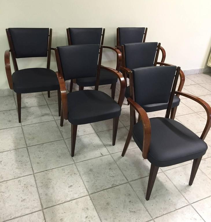 This set of six armchairs was designed and produced in Italy in the 1950s. The are made from walnut with new leather upholstery.