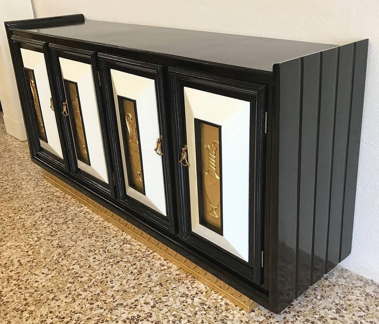 1940s Art Deco sideboard in ebonized oakwood with ivory lacquered details and gold-leafed solid wood engravings, the handles are made of brass and Bakelite. On the inside of the four doors there are some shelves.