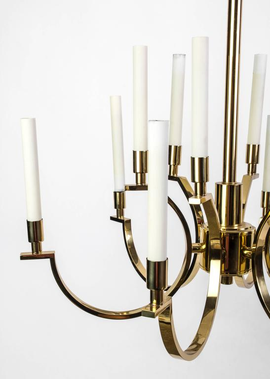 This exquisite Mid-Century Modernist chandelier was designed by Frederick Cooper. It features a two-tier brass frame candelabra form design with elongated candlestick lights. It is in excellent condition.