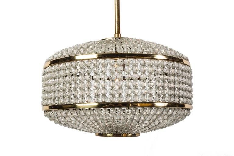 This exceptional pendant was designed by Lobmeyr. It features (2,500) Swarovski pearl crystals surrounding a circular brass base. It is in excellent condition and has been newly rewired.