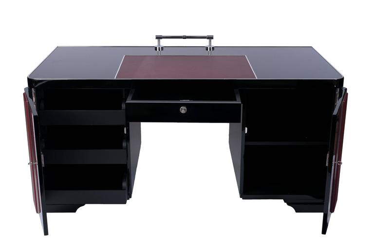 Wonderful Art Deco desk in high gloss piano lacquer with red leather top plate and door inserts and chrome details. Original hardware. This piece was designed to be displayed against a wall, back of piece unfinished.  Made in Belgium, circa