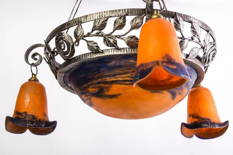 This beautiful Art Deco chandelier was designed and executed by Degué. It features a hand-forged wrought iron base with stylized leaf detailing and floral shaped glass shades in hues of black, amber, sand and gold.