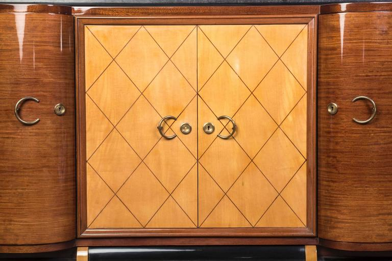 Grand French Art Deco credenza or buffet in palisander with center doors in sycamore and base in black lacquer. The piece is topped with a gray marble. Elaborate hardware that complements the curved design.