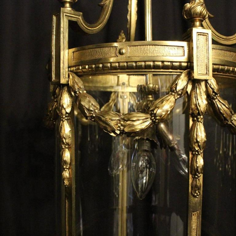 Quality French gilded bronze triple-light antique lantern, the six convex shaped glass panels held within an ornate scrolling framework, having three light fittings with a reeded central column, the bronze frame having decorative Floral swaged