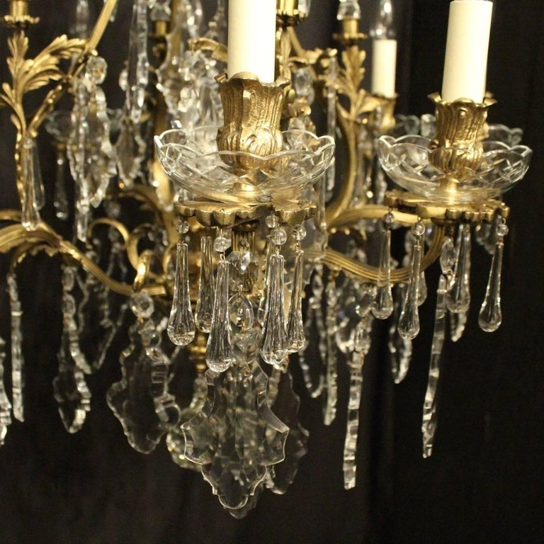 A French pair of gilded bronze and crystal eight-light cage form antique chandeliers, the acanthus leaf reeded scrolling arms with foliated leaf bobeche glass drip pans and reeded bulbous candle sconces, issuing from a cage form interior with a