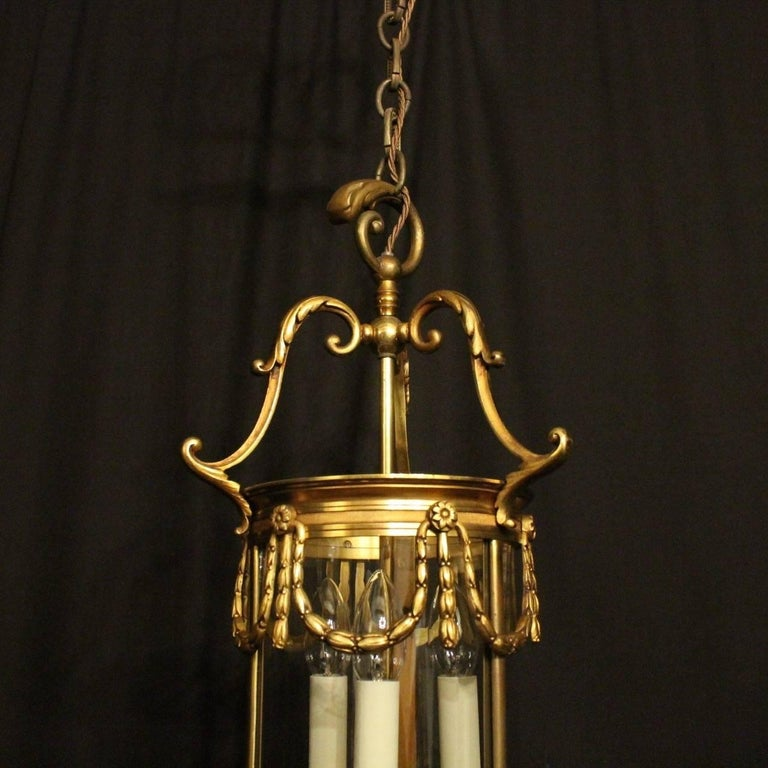 A French gilded bronze triple light convex antique hall lantern, the three light fittings surrounded by three sectional convex glass panels and held within an ornate acanthus leaf scrolling framework with reeded banding, swaged laurel leaf