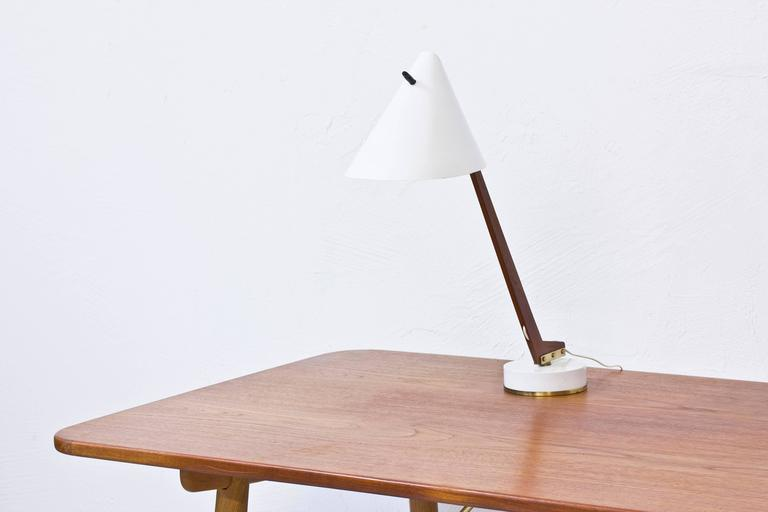 Table lamp model B 54 designed by Hans Agne Jakobsson. Produced by his own company in Markaryd, Sweden during the 1950s. Solid oiled teak stem attached to a white lacquered and brass base and shade with nice brass details. Original light switch on