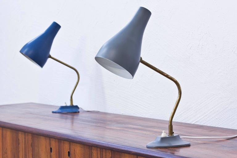 Table lamps produced in Sweden by ASEA. Brass stems with base and shade in painted metal. Adjustable shade and lamp rotating on an axis from the base. Light switch on the base in working order. Very good condition with age related wear and patina.