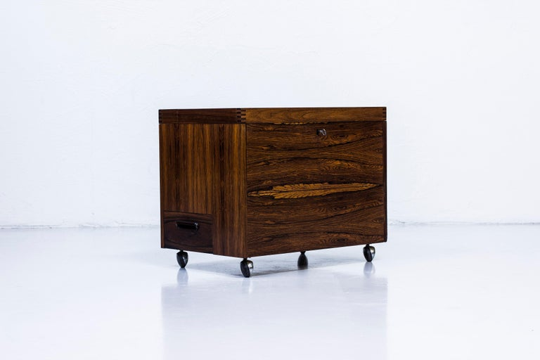 Mini bar designed by Rolf Hesland for Bruksbo tegnekontor. Produced in Norway during the 1960s by Haug Snekkeri. Made from palisander wood on both the inside and outside with brass details. Nice finger joint details on the lid. Lock in working order
