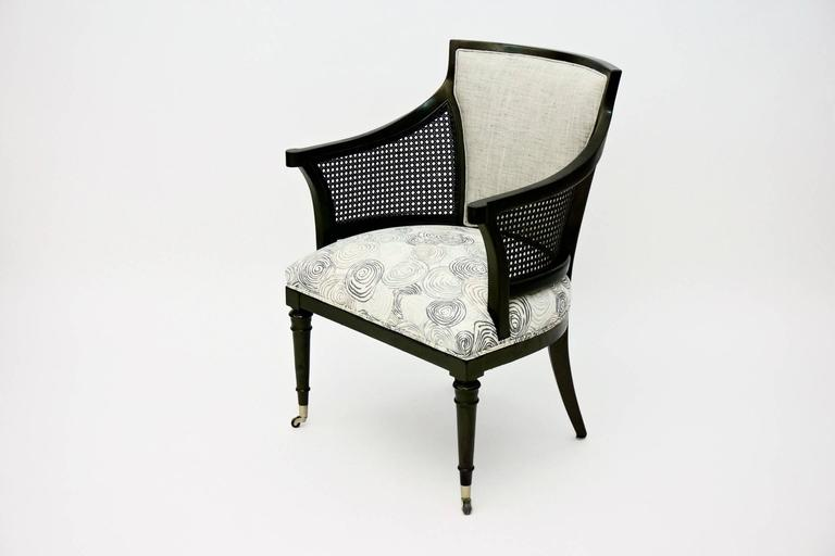Vintage Caned Armchair newly ebonied  and newly upholstered seat and back. Casters on two front legs.