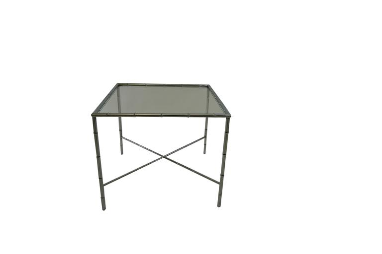 Hollywood Regency faux bamboo metal side table in a nickel finish and clear glass. French 1950's piece in the manner of Maison Bagues. Cross stretchers.