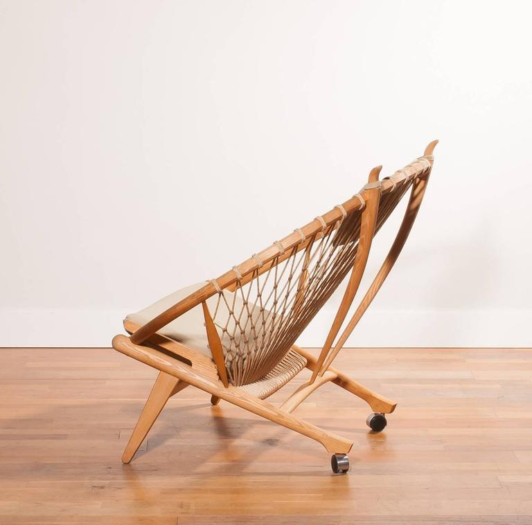 Very beautiful ' Circle ' PP130 chair designed by Hans J. Wegner for PP Möbler. This fabulous chair is made of oak with a net of flags rope secured with steel clips. Under the back legs are wheels and at the top of the backrest two handles, so