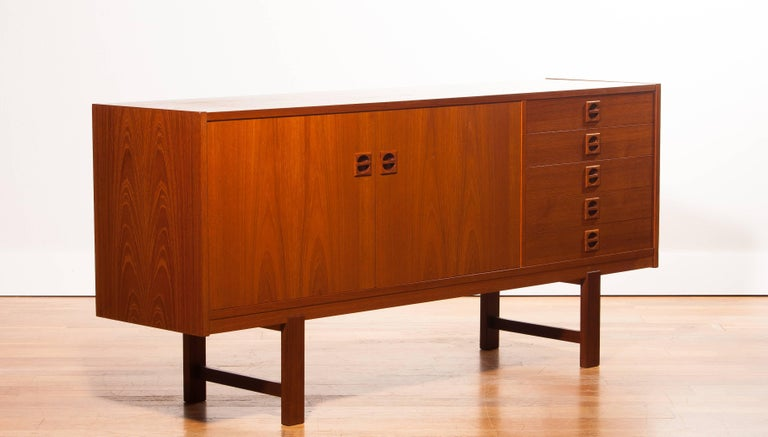 Beautiful sideboard designed by Erik Wørts, Denmark. The cabinet is made of a very nice teak veneer and has five drawers and two doors. It is in a wonderful condition. Period 1950s Dimensions: H76 cm , W 164 cm , D 42 cm.