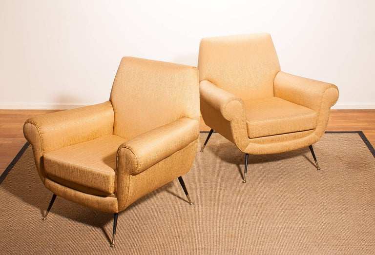 Beautiful and excellent pair of Italian midcentury lounge chairs of the 1950s. With the original brass stiletto legs and gold colored jacquard fabric (later period), all in perfect condition and with a extremely comfortable sit. Designed by Gigi