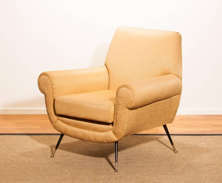 Beautiful and excellent Italian midcentury lounge chair of the 1950s. With the original brass stiletto legs and gold colored jacquard fabric (later period), all in perfect condition and with a extremely comfortable sit.