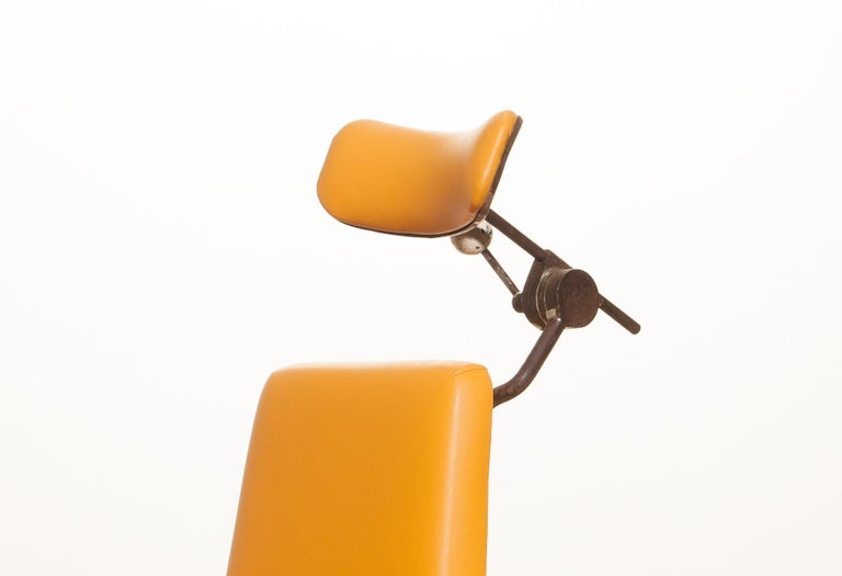 Very nice medical or dentist chair. The frame is made of grey-blue lacquered steel with a new yellow leatherette seating and neck rest. The seating and neck rest are adjustable in height. Some steel parts are rusty what is normal for its