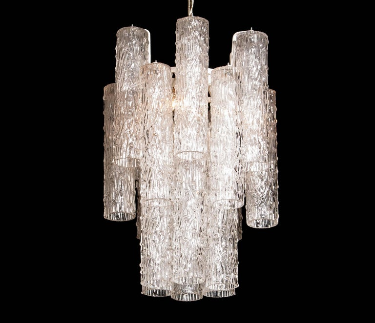 Beautiful chandelier by Toni Zuccheri. This lamp consists of a white lacquered metal frame with 18 clear Murano glass tubes in different sizes. It is in a wonderful working condition. Period 1960s. Dimensions: H 80 cm, ø 40 cm.