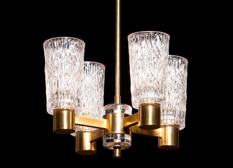 Beautiful chandelier made by Orrefors Sweden. This lamp is made of brass with four clear crystal glass shades. It is in a lovely condition. Period 1950s. Dimensions: H 65 cm, ø 35 cm.